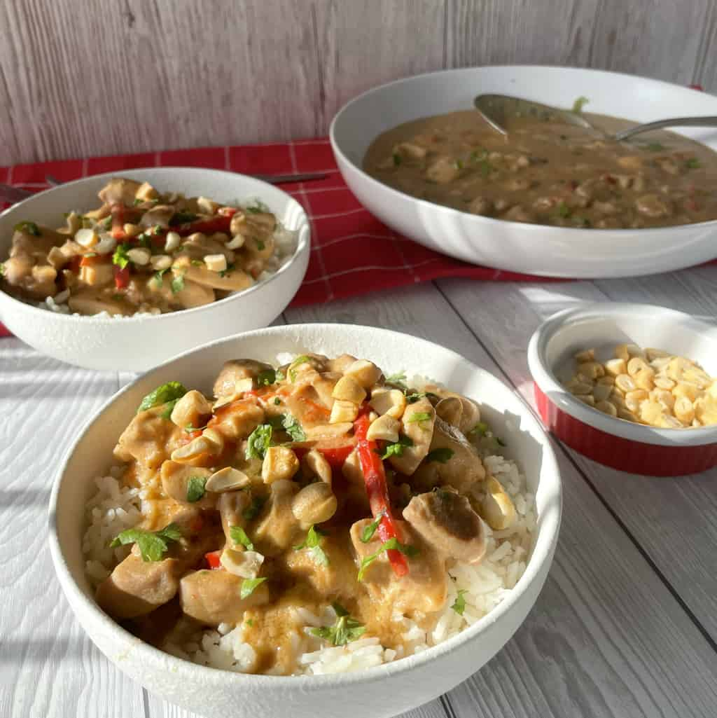 Two bowls of Slow Cooker Satay Chicken in white bowls on rice, with a large bowl of the recipe in the background, garnished with coriander and cashews