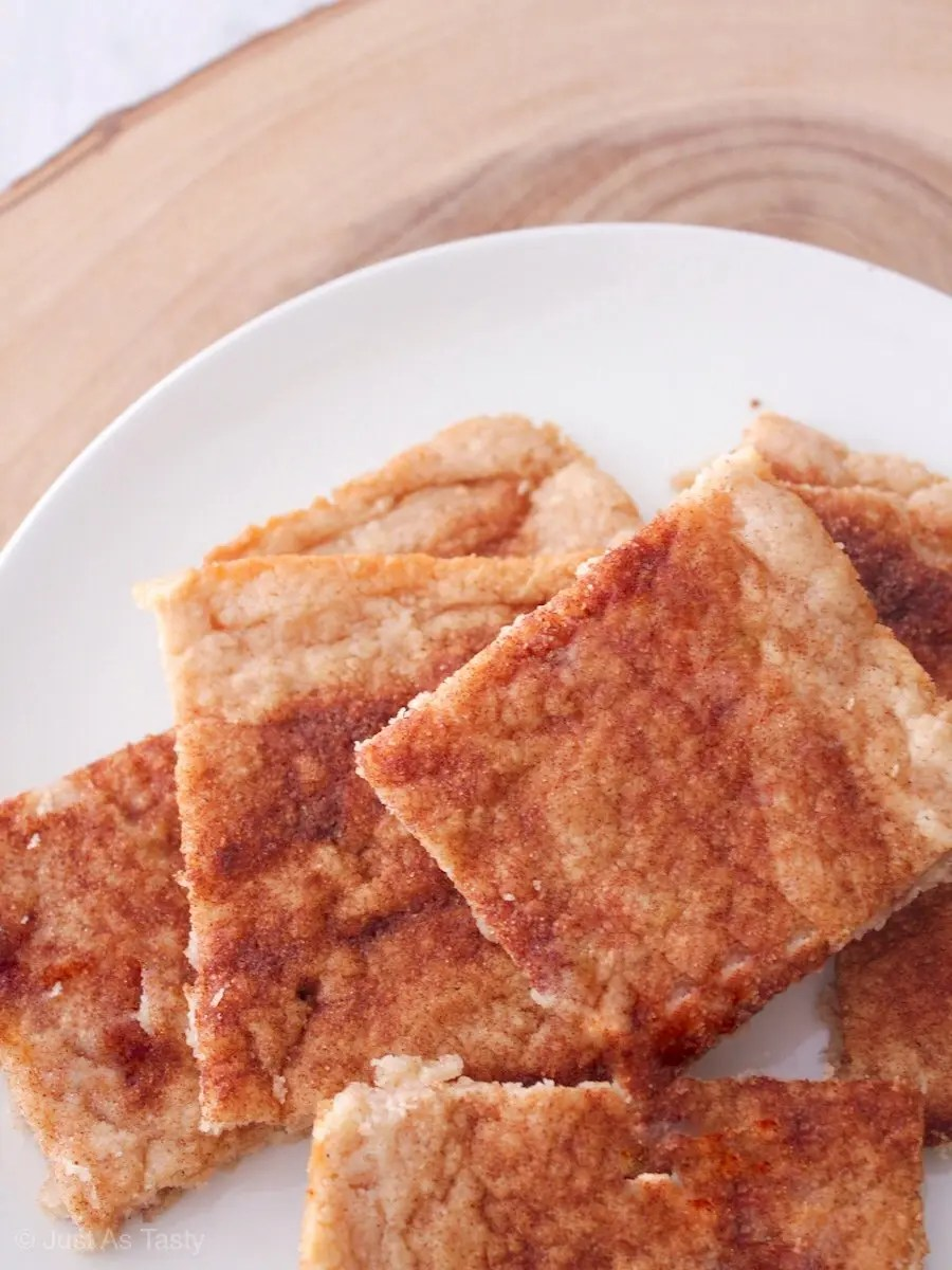 Sliced snickerdoodle bars topped with cinnamon piled on a white plate.