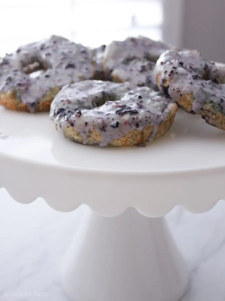 Purple glazed blueberry donuts on a white stand.