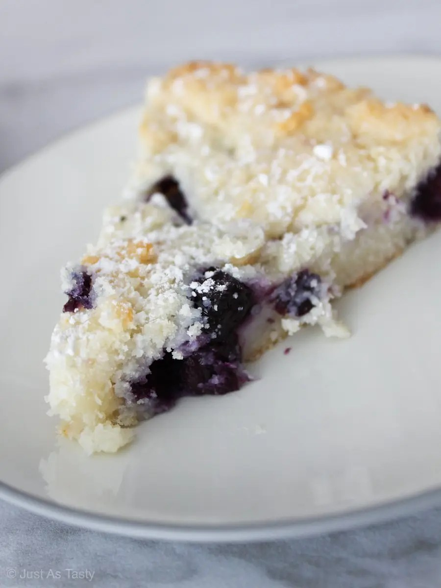 Slice of blueberry cake on white plate