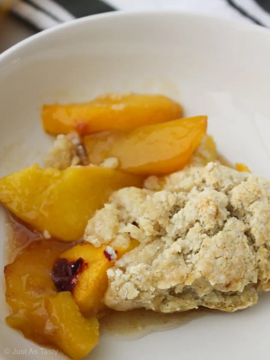 Close-up of homemade peach cobbler with gluten free biscuit topping.
