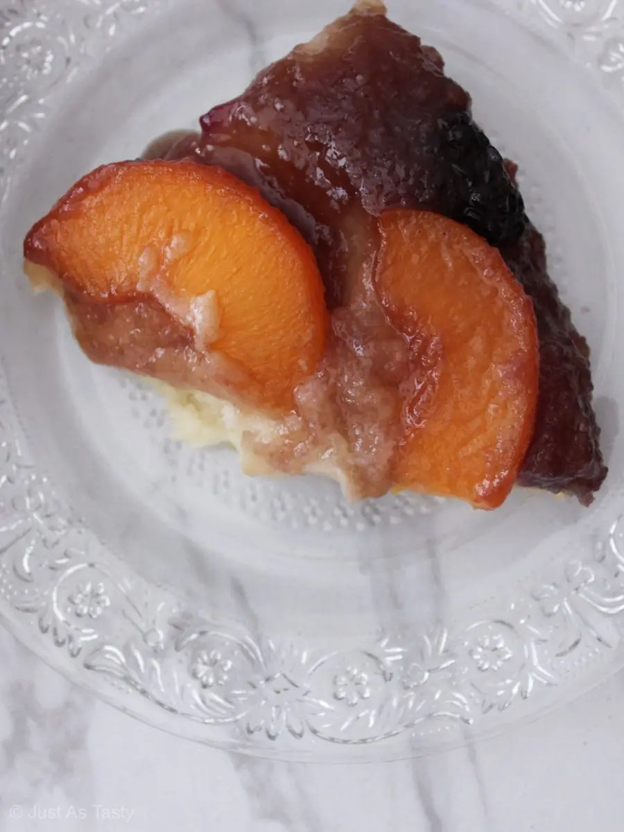 Slice of peach upside down cake on a glass plate.