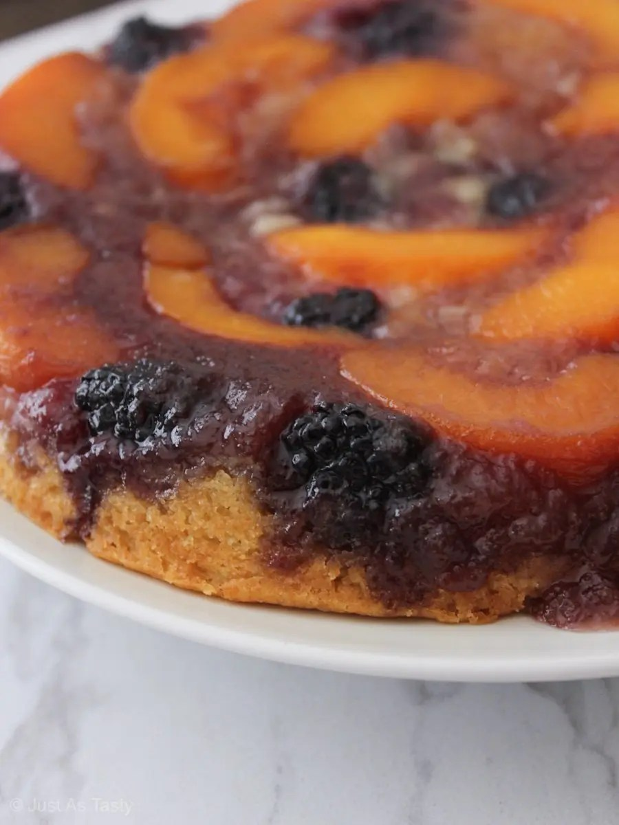 Close-up of peach upside down cake on a white plate.