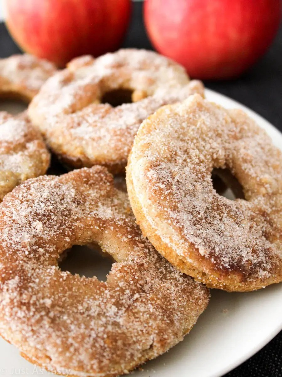 Baked apple cider donuts coated in cinnamon sugar on a white plate.