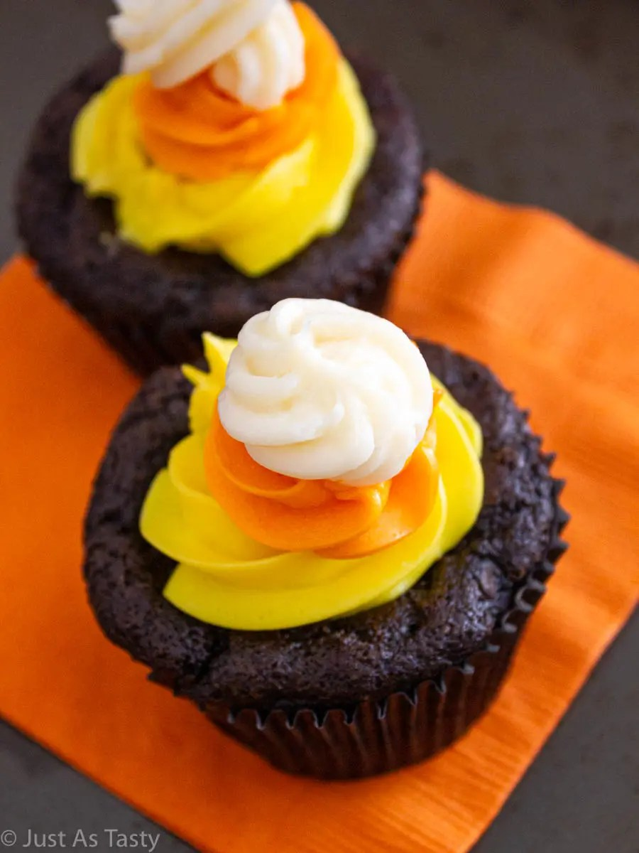 Two chocolate Halloween cupcakes topped with yellow, orange, and white swirl buttercream.