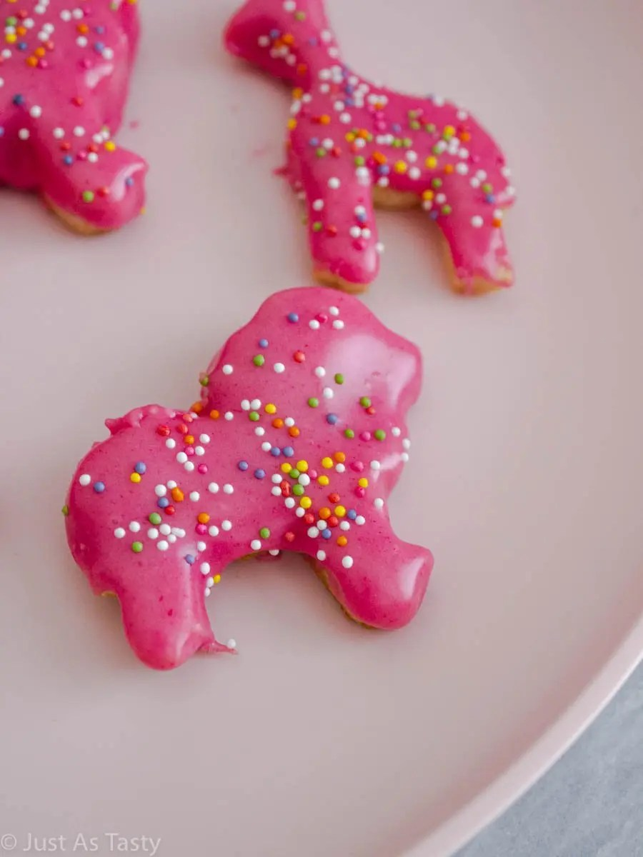 Close-up of a pink circus animal cookie with sprinkles on a pink plate.