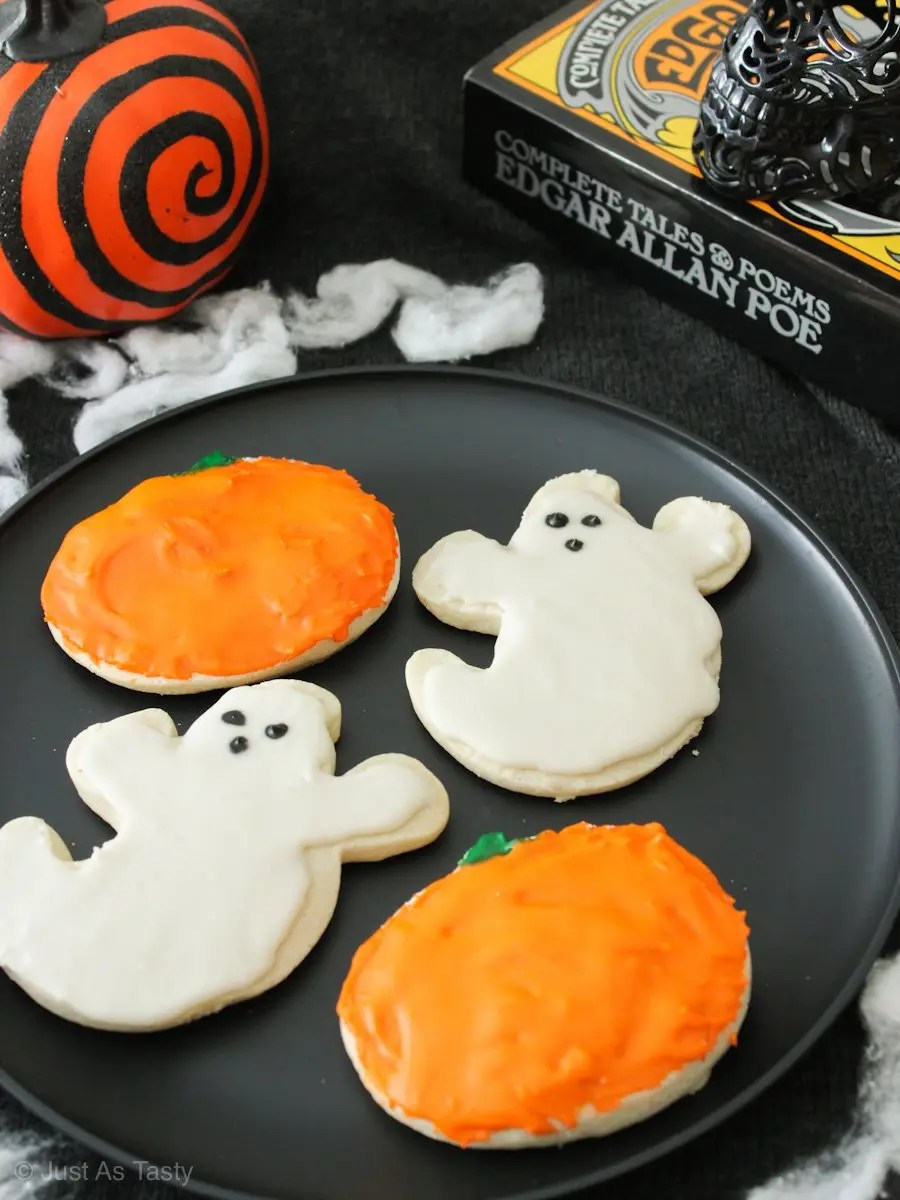 Frosted ghost and pumpkin shaped Halloween sugar cookies on a black plate.