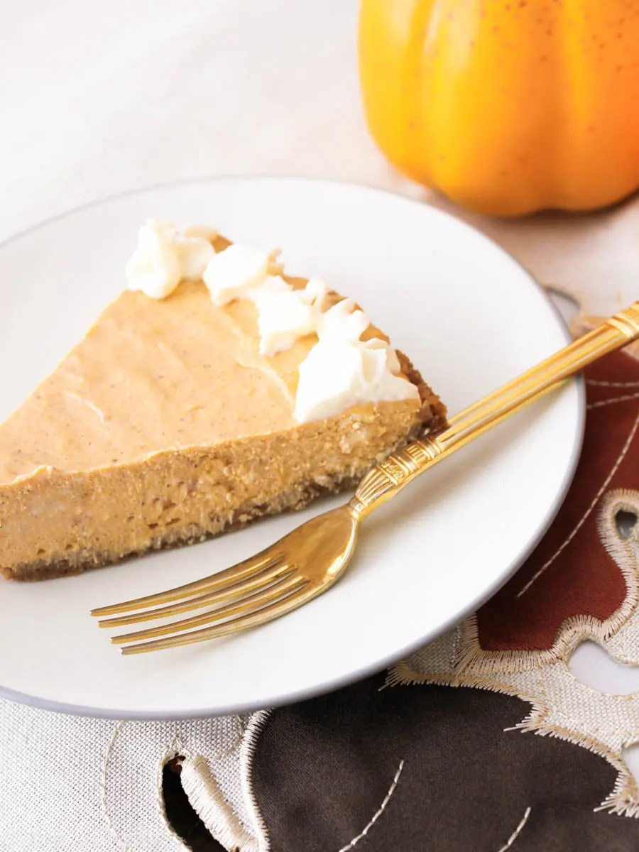 Slice of pumpkin cheesecake on a white plate with a gold fork.