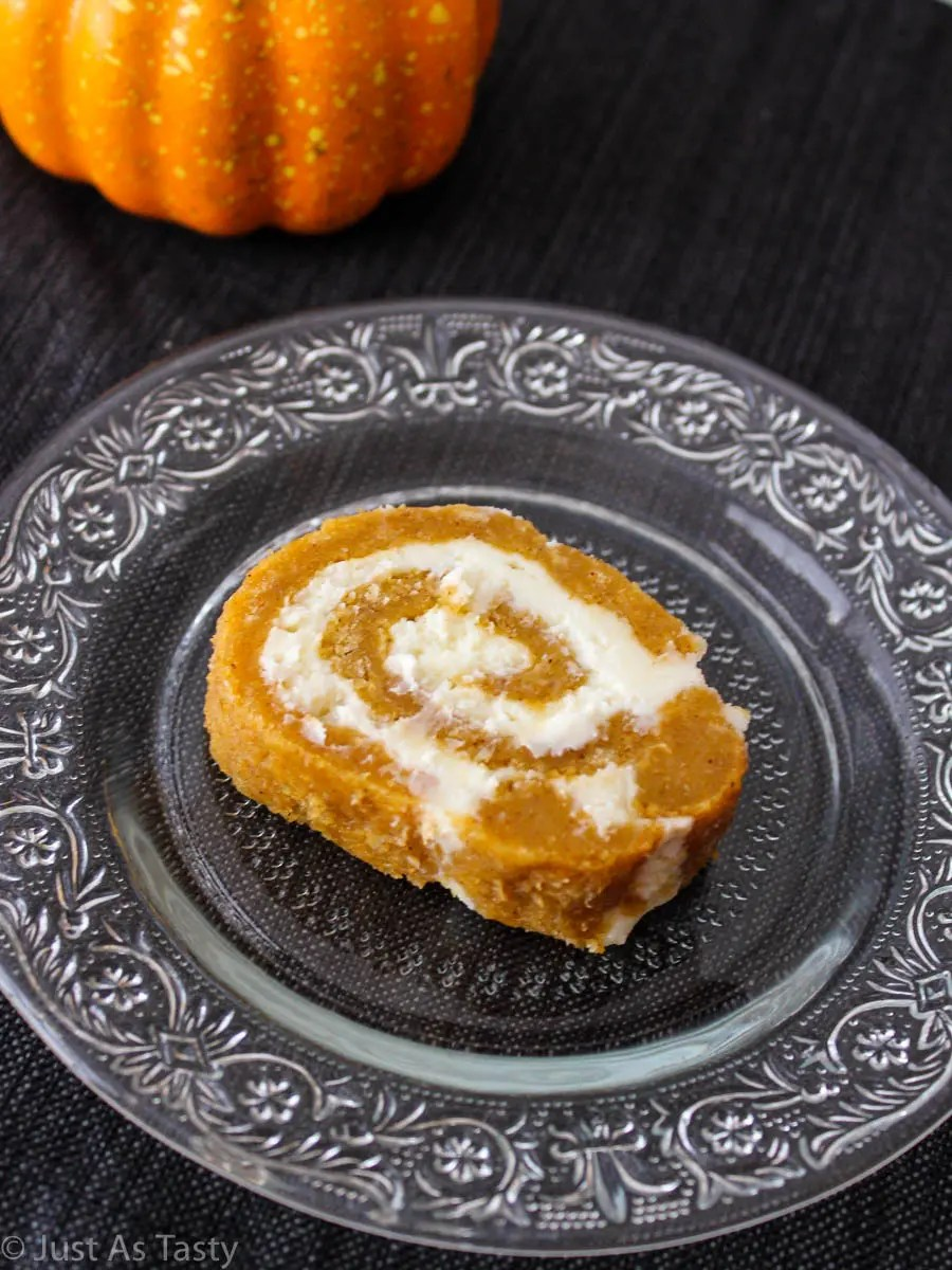 Pumpkin cream cheese roll slice on a glass plate.