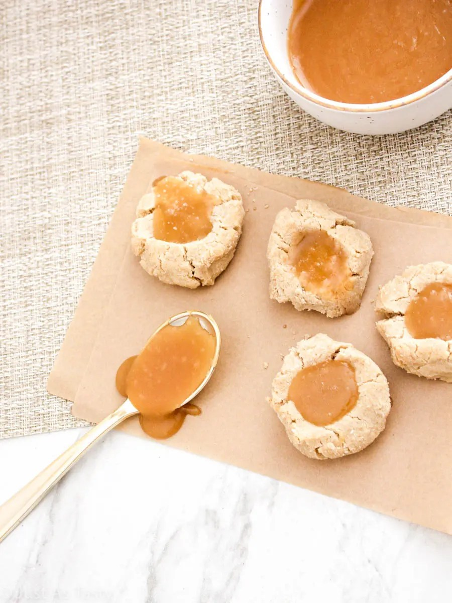 Salted caramel cookies on parchment paper next to a bowl of caramel sauce and a spoon.