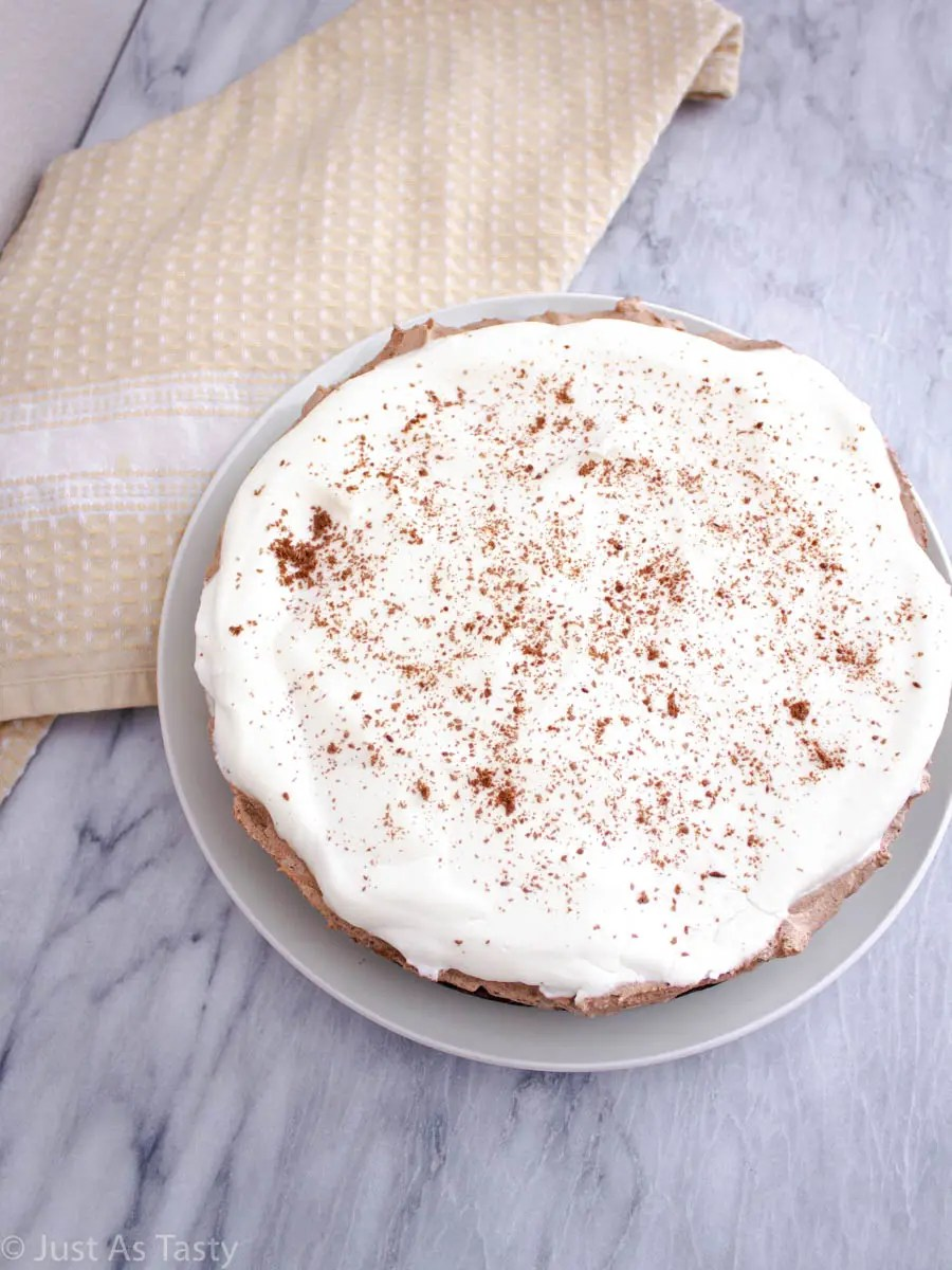 No bake chocolate mousse pie topped with whipped cream and chocolate shavings on a white plate.