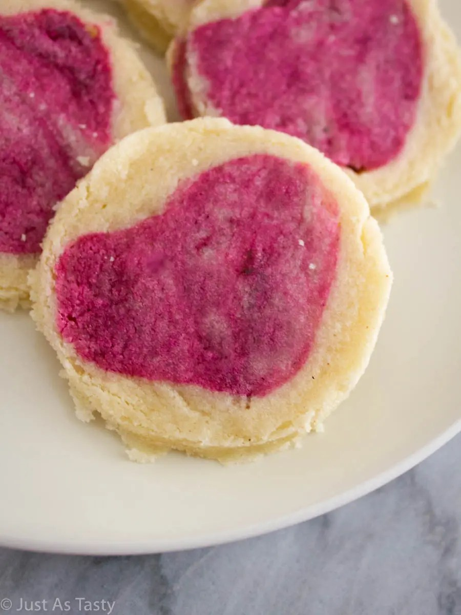 Close-up of slice and bake sugar cookie with a pink heart in the center.