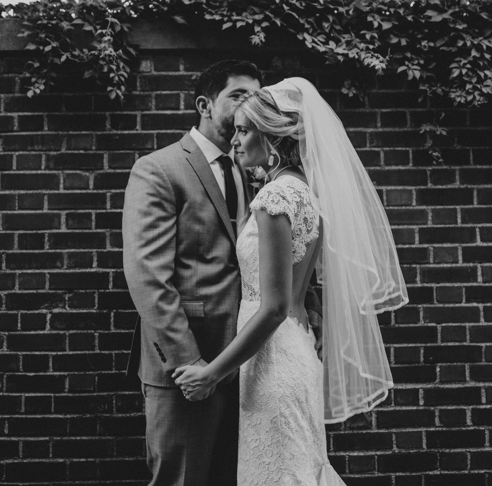 Groom kissing his bride's temple and holding hands gently