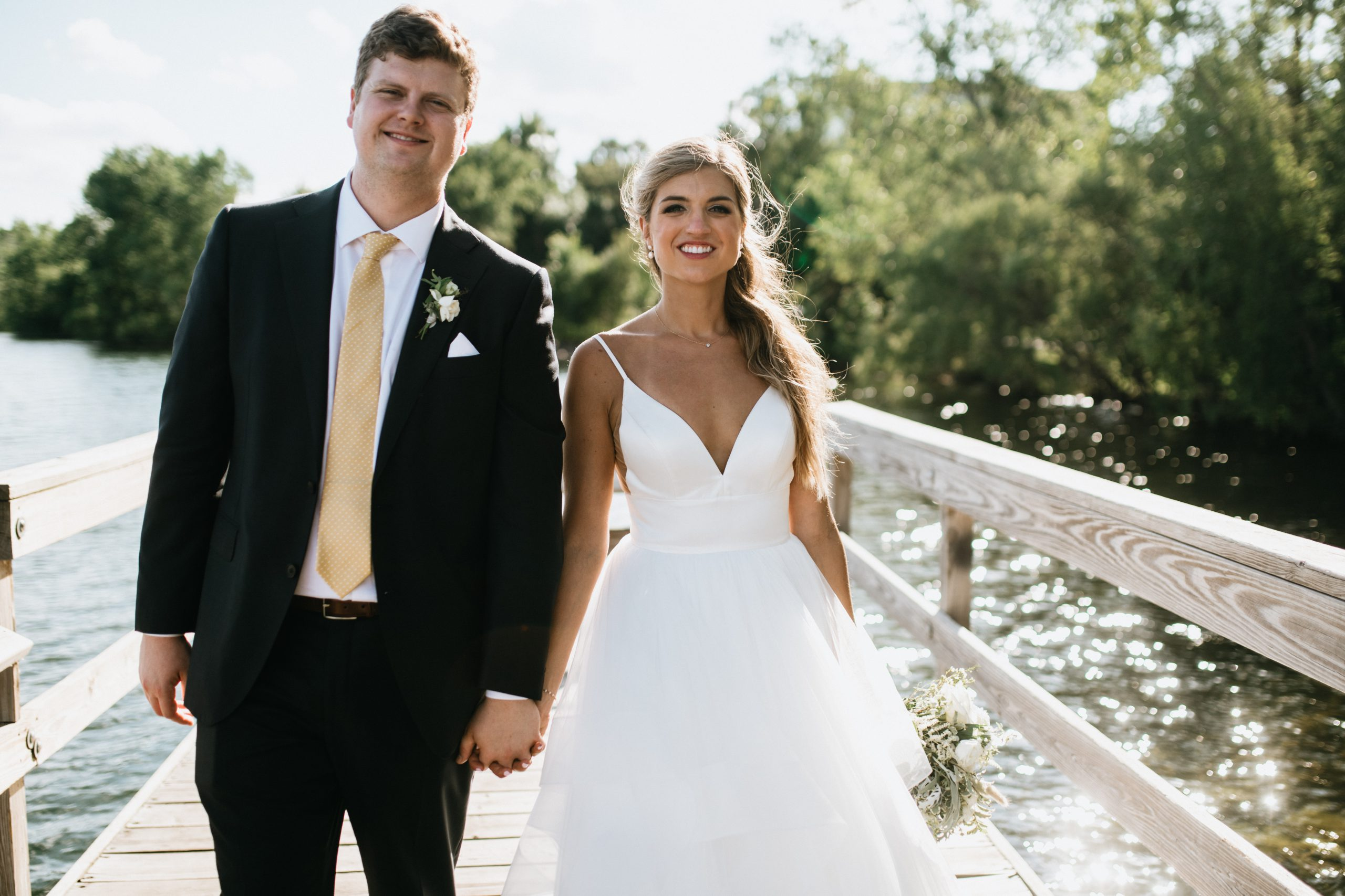 bride and groom walk while holding hands