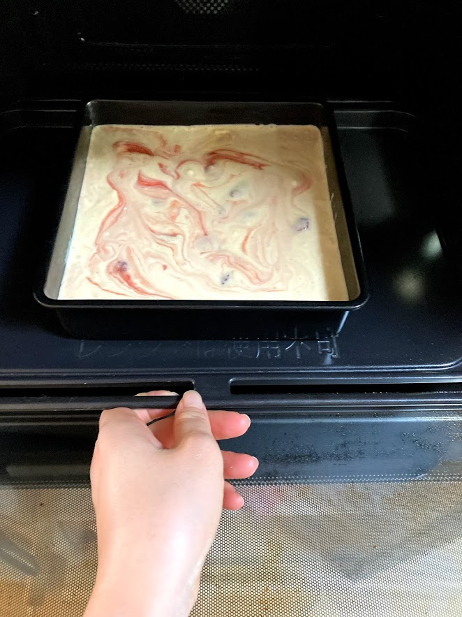 putting cake into oven