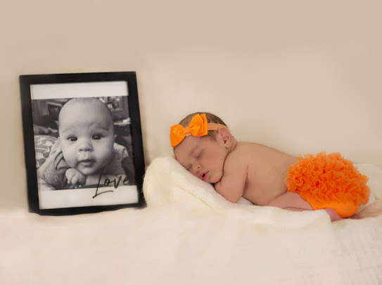 Baby Laying on a Blanket Next to the Photo of Her Baby Brother Who Passed Away