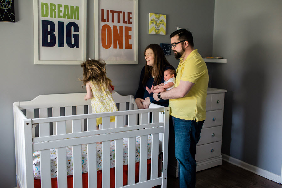 Mom and Dad Holding Newborn as Her Sister Jumps in Her Crib