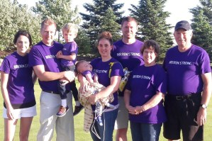 Sarah holds her son Brecken while surrounded by family during Brecken's first annual charity golf tournament.