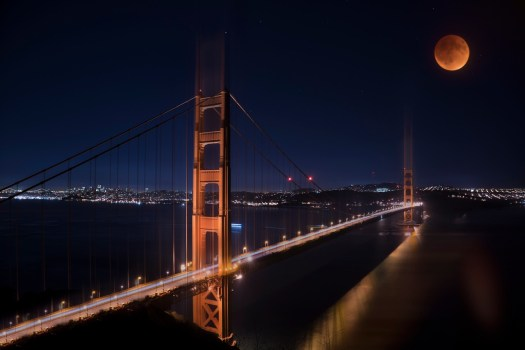 """While in San Francisco I just """"had"""" to """"do the bridges"""". By that I mean, drive over and take pictures, ...just like everybody else. I went through the motions but I didn't have my heart into it. I mean, it's only been done one-million-and-four-hundred-and-sixty-two-thousand-and-seven-hundred-and-ninety-two times (excluding Andriod devices). Not like it's popular or anything. Even when I showed up at 5AM on a MONDAY MORNING there were three other photographers there. I mean, don't these people have anything better to do than get up early on a MONDAY morning and take yet another picture of the bridge? Good grief, some people. Anyway, I stuck around looking for a unique angle that hadn't been done before, how hard could that be? Those other pesky photographers finally left and I was about also when I looked back and noticed that the Blood moon had popped up over the bridge. How lucky is that? I quickly took my shot and I think I may be the only person in the world to have a shot of the Blood Moon over the Golden Gate. I'm currently in negotiations with Hogwarts to have this hung in the grand hall, but I wanted you all to be the first to see it."""