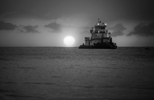 A tug in the Gulf of Mexico just off the beach in central Florida as the sun sinks.  When I looked closely I noticed the tug was from Texas. That's probably about five hundred miles north west of here. Then I noticed that it had a satellite dish and several decks. It occurs to me the occupants can live on this for quite some time. It was probably here on a job as I was standing next to a large barge on the beach which is being used to dismantle an old pier. Anyway, all that aside I positioned myself to catch the tug close to the sun as it went down.  The end of another day of work for the crew as they watch satellite TV and eat dinner in the galley.