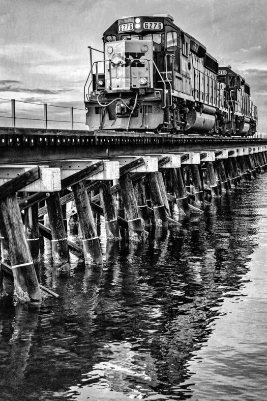 A train passes over the Manatee River in Bradenton Florida. These engines were on their way to pick up oranges for the Tropicana plant down the line. It happens every day at the same time and each time it goes by there are a few people lined up to watch. The people wave, the conductor waves and life goes on as it has for decades. Where would we be if not for the railroads?