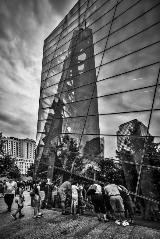 Last summer I was at the 911 memorial right after it opened to the public. These people are looking into into the museum which is all underground and above them In the glass is the reflection of the newly constructed freedom tower.