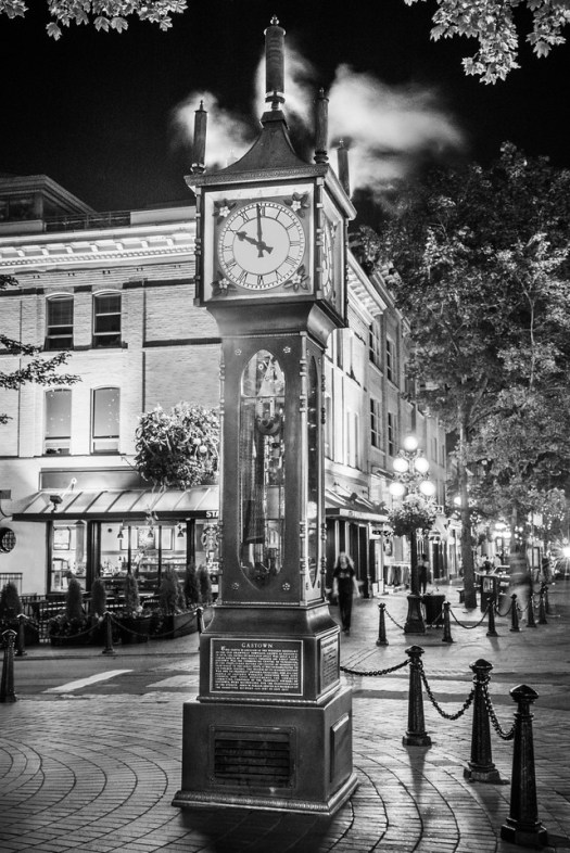 "This is a well-known steam clock in the Gastown section of Vancouver. I took this as I walked by on a warm summer evening last August.  Every ten or fifteen minutes the clock will begin blowing steam and the attached whistles will sound. As silly as that sounds it's really fun to wait it out, like waiting for a geyser. This is one of my favorite sections of town; with the old architecture it stands in contrast to the ultramodern architecture just two blocks away. It's said there used to be tunnels below the city that were used by the well heeled. Presumably they were used to convey ""businessmen"" to the more seedy sections of town to satisfy out their whims and pleasures. Though with the way Vancouver has grown, what was once ""seedy"" is now the pricier section of town. Perhaps if the tunnels still exist they are used in reverse?"