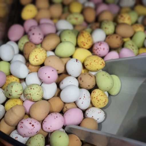 Milk chocolate mini eggs scoop in the plastic free snacks and treats section Just Gaia zero waste grocery in Halifax, West Yorkshire