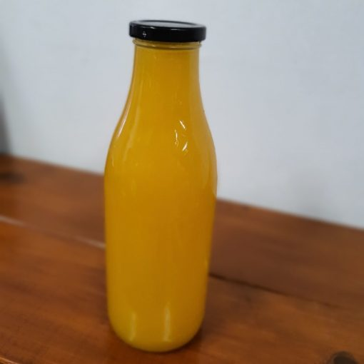Freshly squeezed orange juice bottle in the plastic free snacks and treats section Just Gaia zero waste grocery in Halifax, West Yorkshire