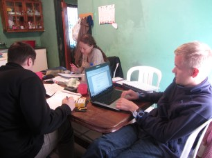 Justin, Steffen and Kristina preparing for teachings; the kitchen table became the community desk =)
