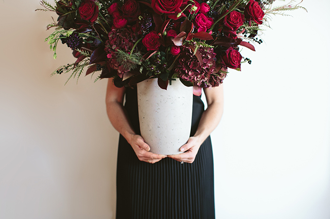 Luxe Holiday Floral Inspiration | Moody Oversized Winter Flower Arrangement in a cement vase with Black Magic Roses, Black Baccara Roses Gem and Lace Spray Garden Roses, Liqustrom, Hypericum, Allium, Lisianthus, Scabiosa, Chocolate Lace, Cotinus, Photina and Grevillea by Rebecca Dawn Design // JustineCelina.com