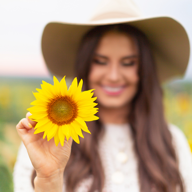 September 2018 Soundtrack | Girl Holding a Sunflower in the Bowden Sunmaze, Alberta, Canada | Calgary Lifestyle Blogger // JustineCelina.com