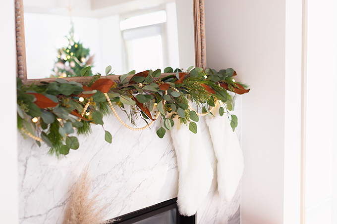 Apartment Friendly Modern Holiday Decor   Canadian Tire CANVAS Pre-lit Eucalyptus Leaves Garland with added greenery, magnolia leaves and wooden beads   Marble Fireplace   Bohemian, Mid Century Modern Holiday Decor   Bohemian Holiday Home Tour 2018   Caramel Mid Century Modern Leather Couches   Canadian Tire CANVAS Ornaments // JustineCelina.com