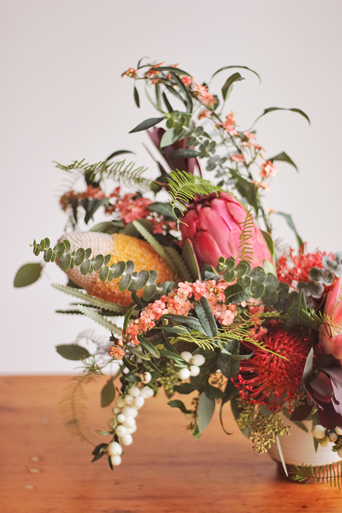 An Eclectic, Globally Inspired Arrangement featuring Euphorbia, Seeded Eucalyptus, Foraged Snowberries, Baby Blue Eucalyptus, King & Queen Protea, Leucadendron, Silver Dollar Eucalyptus, Pin Cushion, Coral Fern, Banksia | Pantone Colour of the Year 2019 Living Coral Inspiration // JustineCelina.com + Rebecca Dawn Design