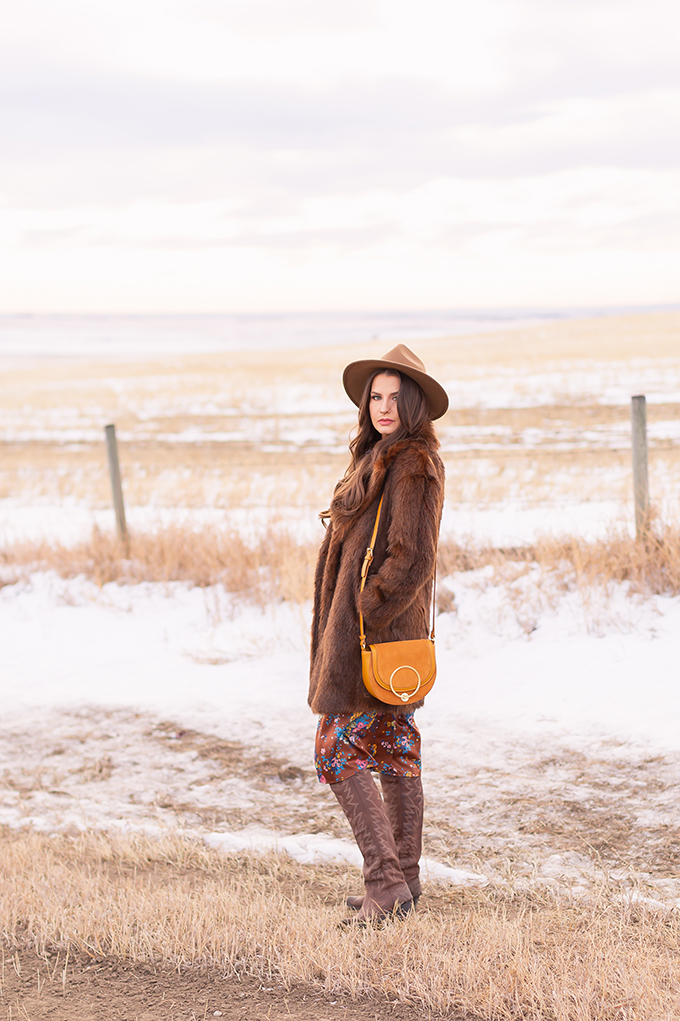 Winter 2019 Lookbook | Bohemian Rhapsody: How to Style Midi Dresses for Winter | Brunette Girl Standing in a Country Field at Sunrise Wearing a Brown Floral Dress, Faux Fur Coat, Brown Wide Brim Hat, Western OTK Boots and a Mustard Cross Body Bag | Bohemian Winter Style Ideas | Pantone Spring Summer 2019 Fashion Ideas // JustineCelina.com