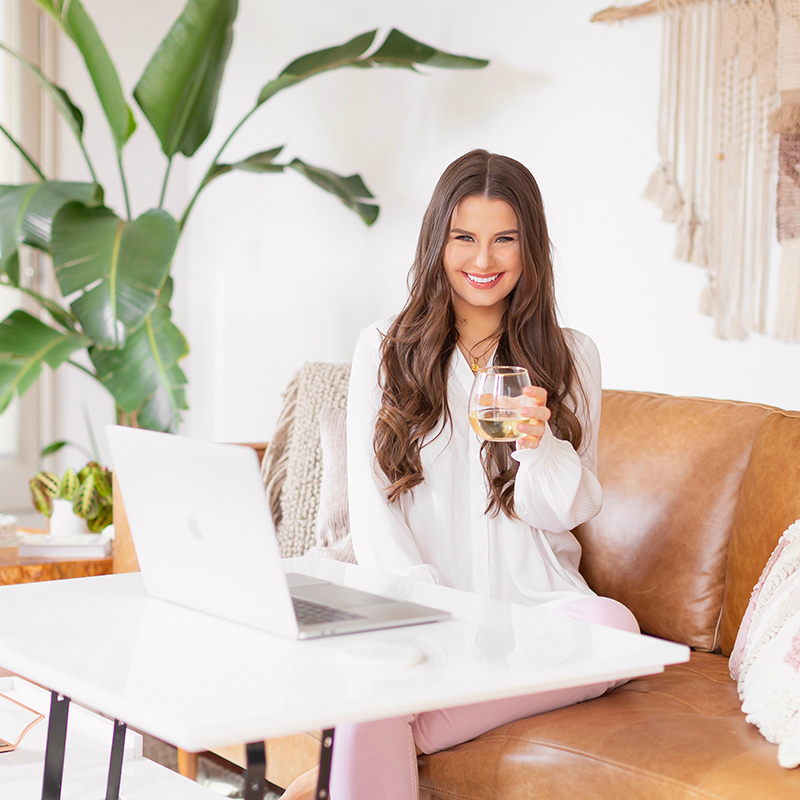 Meet Justine // Justine Celina Maguire | Calgary Lifestyle Blogger | Justine Celina Maguire Home Office Spring 2019 | Justine Celina Maguire's Mid Century Modern, Bohemian Apartment in Calgary, Alberta, Canada | JustineCelina Home Office | Female Entrepreneur Working from Home with a glass of wine | Brunette woman smiling with a glass of white wine working on a MacBook Pro | Structube EVO Coffee Table | Calgary, Alberta, Canada Creative Lifestyle Blogger and Entrepreneur // JustineCelina.com