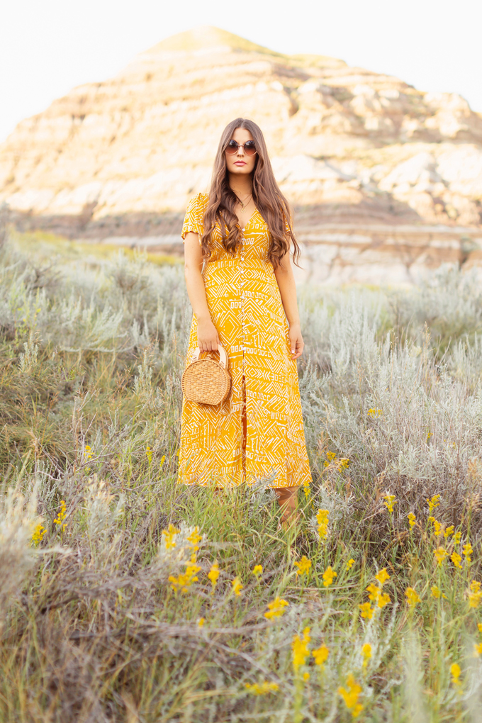 LATE SUMMER 2019 LOOKBOOK | Mustard Moment: How to Transition Midi Dresses into Autumn | How to Wear Summer Clothes in Fall | Brunette Woman wearing a button-down mustard Aztec print midi dress with a woven rattan bag and nude espadrilles | Top Summer to Fall 2019 Transitional Trends and how to wear them | HooDoos, Drumheller Bandlands, Alberta | Calgary Fashion Blogger // JustineCelina.com