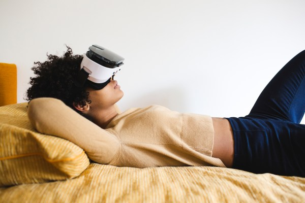 Woman wearing VR goggles on her bed