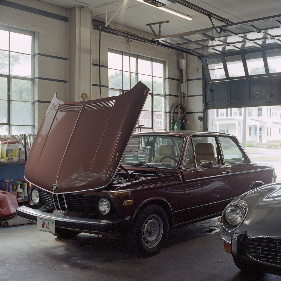 Color photo of a BMW 2002 with it's hood up in Ava Restoration Services