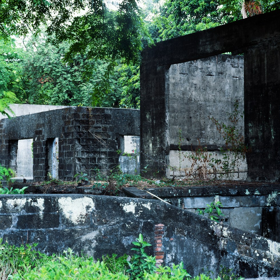 Decaying buildings at Fort Santiago surrounded by trees.