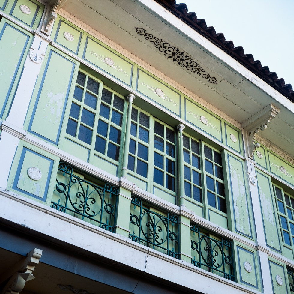 The windows and surrounding details of a colorful old building in Intramuros