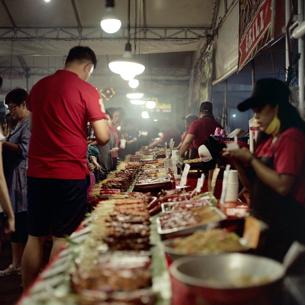 Looking down the row of all the food options at a night market