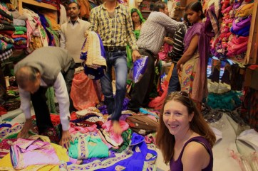 Jen choosing which saree to buy in the Agra Bazaar