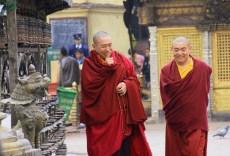 Buddhist Monks strolling around the stupa's prayer wheels