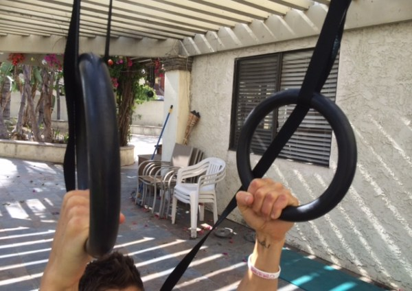 Man holding on to gymnastic rings that are attached to a wooden beam on an outside patio