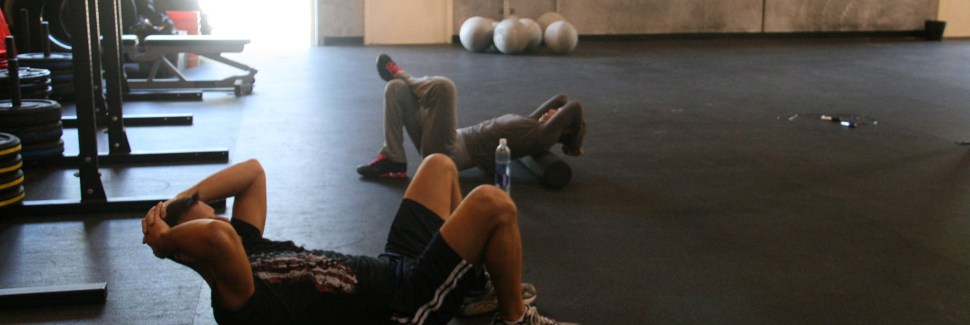Two men laying on foam rollers inside of a Crossfit gym