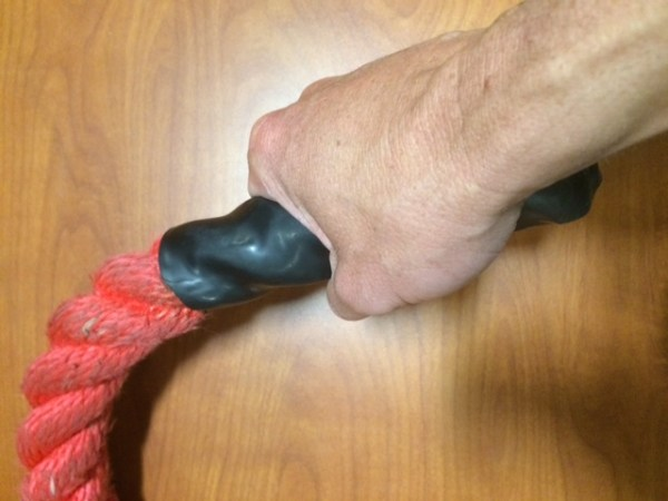 A mans right hand gripping a red battle rope