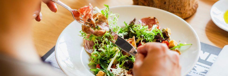 Man eating a salad at a table