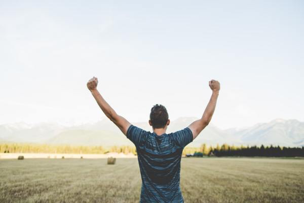 man holding up arms in celebration