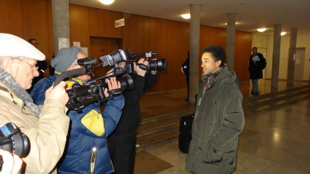 """Prozessbeginn gegen Dr. David Schneider-Addae-Mensah beim Amtsgericht Karlsruhe mit großer Kamerabegleitung wegen einer angeblichen Beleidigung . Der """"Angeklagte"""" steht offen Rede und Antwort."""